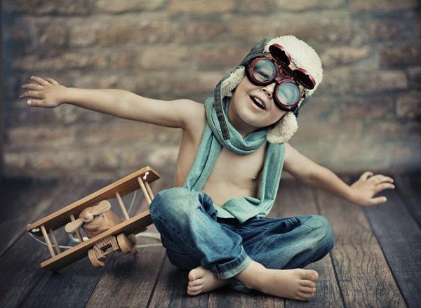 boy pretending to fly wearing old aviator headgear